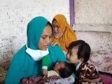Siti Zainah bersama anak dan bayi yang baru dilahirkannya. 9Sumber: telisik.id).