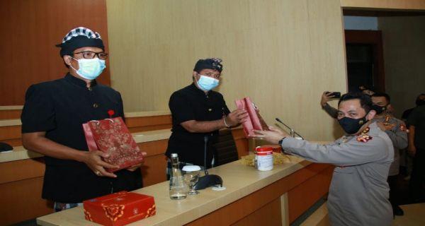 Kapolri Jenderal Pol. Listyo Sigit Prabowo (kanan) memberikan penghargaan kepada dua pecalang yang berprestasi. (Sumber: ANTARANEWS/HO-Polri).